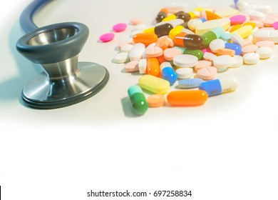 Numerous colorful and vivid drugs in form of tablet,capsule with blue stethoscope and orange light with copy space