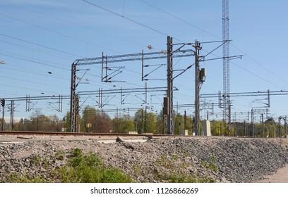 Numerous overhead lines above train tracks in Helsinki, Finland.
