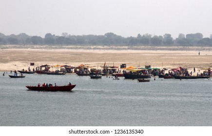 Numerous pilgrims perform ablution and praying in the sacred water of the river Ganges. Sandbanks of the river in a state of winter low water opposite the city Varanasi. Sheds for palmers