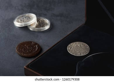 Numismatics. Old collectible coins made of silver, gold and copper on a wooden table.