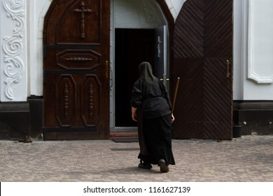 A nun in black cassock with a stick from the back. A nun dressed in black clothes enters the church door. An old nun in a black cassock at the monastery approaches the door.