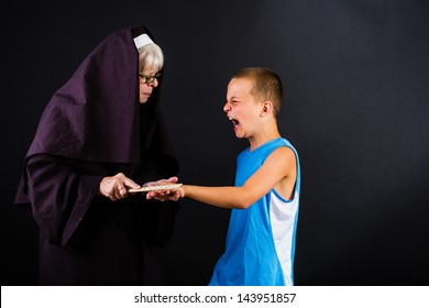 A nun hitting a young boy on the knuckles with a ruler.