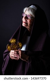 A nun holding a cross and looking up