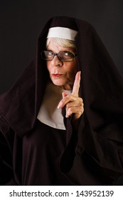 A nun holding up her finger in a gesture of patience.