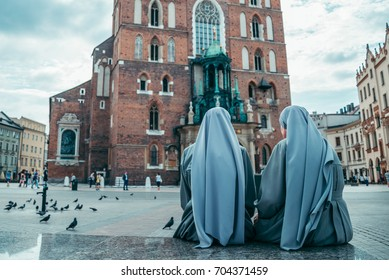 nun looking on old church in dramatic weather pigeons flying in clouds