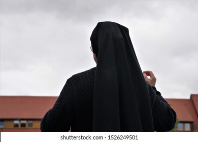 A Nun, Seen From Behind, Looking At The Old Monastery, Germany. Gray Autumn Day Background.