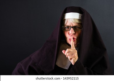 A nun shushing for quiet with her finger