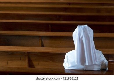 The nun sits in the church and prays to God. A nun in traditional white robes meditates in a Christian cathedral. Prayer to Jesus.