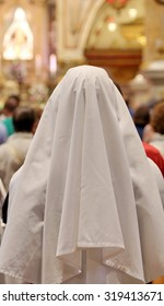 nun with white veil in prayer inside of the Christian Church during mass.