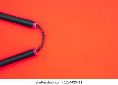 Nunchaku for training on a red background. Copyspace