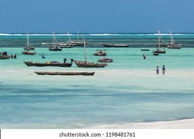 Nungwi beach, Zanzibar - 10 December 2017: Children playing in the water among fishermen boats