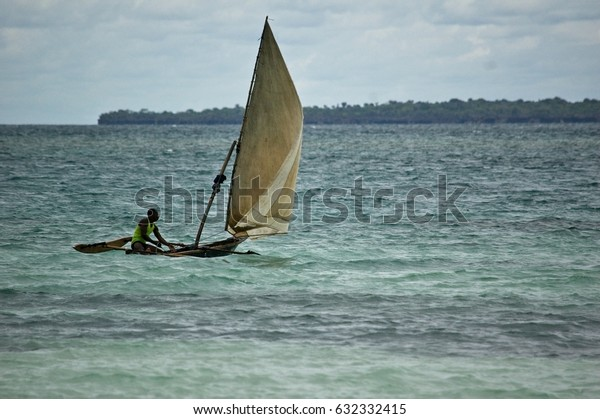 Nungwi beach, Zanzibar, 30 April 2017: A local sailing in a traditional catamaran boat off the water from Nungwi beach.