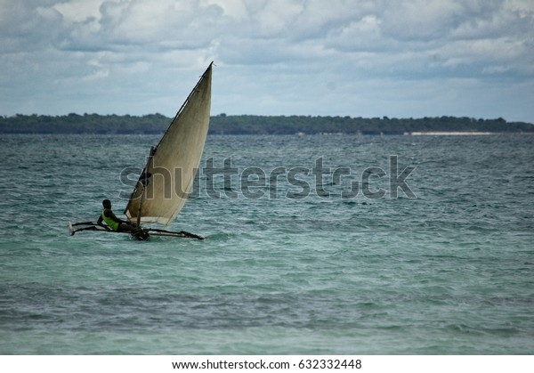 Nungwi beach, Zanzibar, 30 April 2017: A local sailing and manoeuvring his traditional catamaran boat off the water from Nungwi beach.