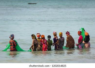Nungwi, Zanzibar in 3 June 2018: Women fishing in ocean with lots of boats in background. Storm clouds in Nungwi- Zanzibar, Tanzania