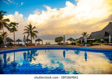 Nungwi, Zanzibar - December 22 2020: Luxury hotel sunrise light pool view Exotic tropical lanscape with amazing clouds