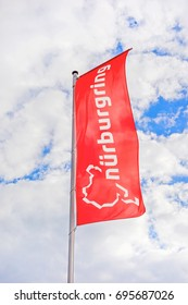 """Nurburg, Germany - May 20, 2017: Flag at race track Nurburgring info center entrance, labeled with """"Nurburgring"""" and logo"""