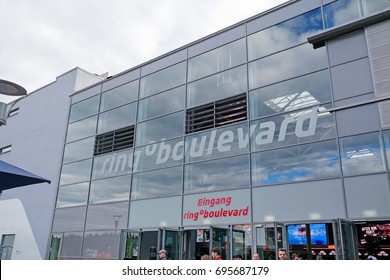 """Nurburg, Germany - May 20, 2017: Race track Nurburgring, people in front of entrance """"ring boulevard"""" - glass facade building"""