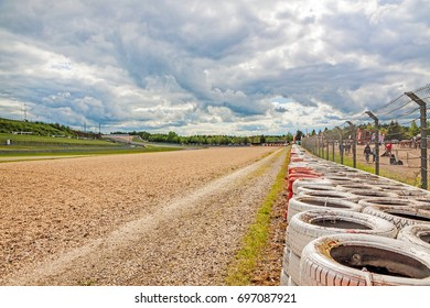 Nurburg, Germany - May 20, 2017: Race track Nurburgring - gravel bed beside speedway with orange, white tyre stack