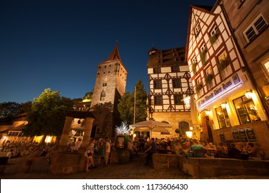 Nuremberg, Bavaria / Germany - 08/27/2016: People sitting on the ground of old town by night, with houses of typical german architecture on the background