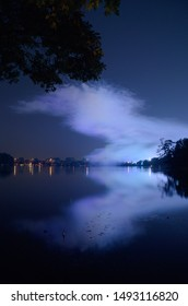 Nuremberg, Bavaria / Germany - August 30, 2019 Opening fireworks to the autumn folk festival over the Dutzendteich. Double fireworks thanks to the reflection on the water. Smoke on the water.