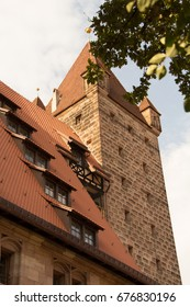 Nuremberg Castle With Red Pile roofs and and an old tower framed by the leaves of a tree, shot in the forenoon of a sunny summer day