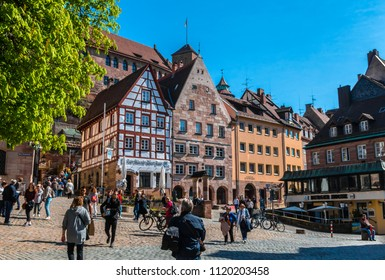 Nuremberg, Germany - April 14, 2018: Tourists on the Tiergarten square in Nurnberg near Albrecht Durer house. Tiergartnerplatz at spring sunny day. Medieval european architecture.