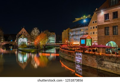 Nuremberg, Germany - December, 05, 2018: Christmas market in the old town of Nuremberg at Pegnitz river at night.