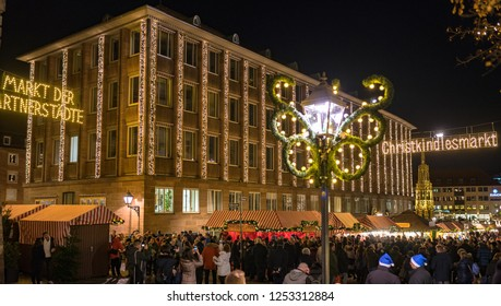 Nuremberg, Germany - December, 05, 2018: Christmas market, the most famous Christkindlesmarkt. Many people tourists visit traditional Christmas market in the old town of Nuremberg at night.