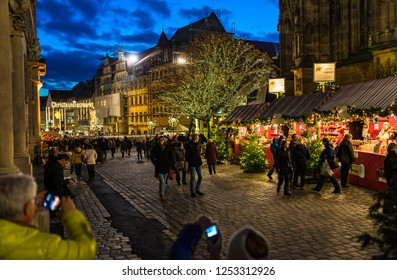 Nuremberg, Germany - December, 05, 2018: Tourists, people visit Christmas market, the famous Christkindlesmarkt in the old town of Nuremberg at night.