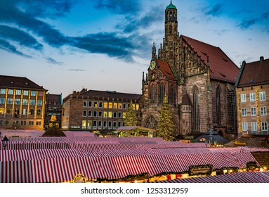 Nuremberg, Germany - December, 05, 2018: Christmas market, the famous Christkindlesmarkt in the old town of Nuremberg at evening. With view of the historic old church cathedral Frauenkirche.