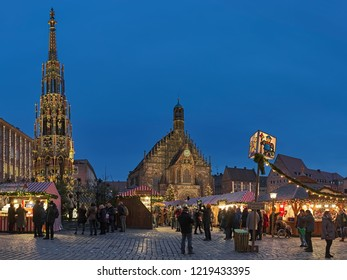 NUREMBERG, GERMANY - DECEMBER 13, 2017: Christkindlesmarkt at Hauptmarkt (Main Market Square) in dusk. This is one of the largest Christmas markets in Germany and one of the most famous in the world.
