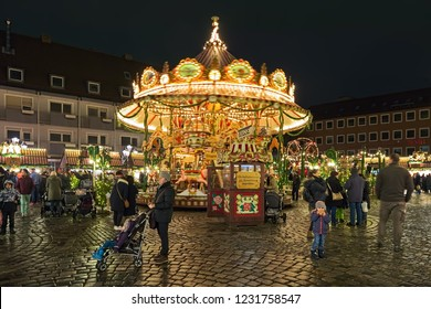 """NUREMBERG, GERMANY - DECEMBER 13, 2017: Nostalgic two-tiered carousel at Children's Christmas Market """"Kinderweihnacht"""" on Hans-Sachs-Platz in dusk. This Christmas market has been going since the 1999."""