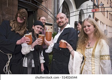 NUREMBERG, GERMANY - DECEMBER 17, 2013: Young people dressed in the medieval style, toast at the door of a tavern, in the old town