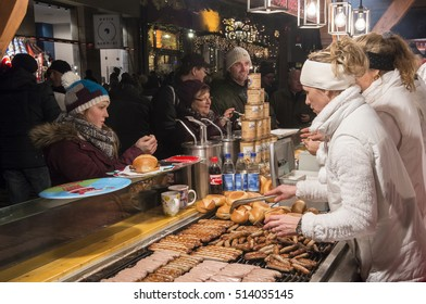 NUREMBERG, GERMANY - DECEMBER 17, 2013: Women serving sausages, at a food stall, at the Christmas market