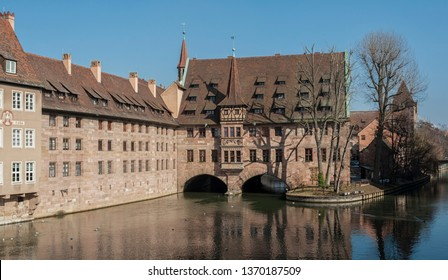 NUREMBERG, GERMANY - MARCH 04, 2018: Heilig-Geist-Spital (Hospice of the Holy Spirit) in Old Town Nuremberg. View from the Museum Bridge on the River Pegnitz - Nuremberg, Bavaria - Germany