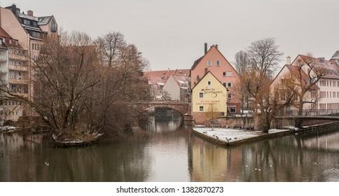 NUREMBERG, GERMANY - MARCH 04, 2018: Houses and bridge reflected in a river in the old town of Nuremberg seen from Henkersteg covered bridge across Pegnitz river toward Trodelmarkt bridge - Nuremberg
