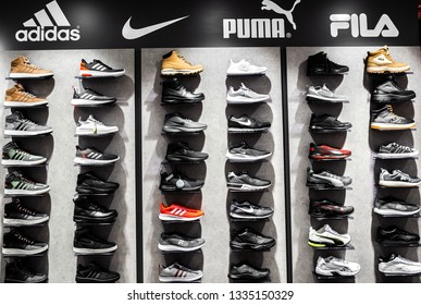 Nurmberg, GERMANY - February 27, 2019: The NIKE, ADIDAS, PUMA and FILA black man sneakers on the shell in the shop. Fashionable foot wear shoes.