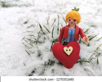 Nurmber,Germany - December29, 2018 : A Lego girl model is standing on white puffy snow, she has a red heart shape in front of her, on the red heart is a wooden botton on it.