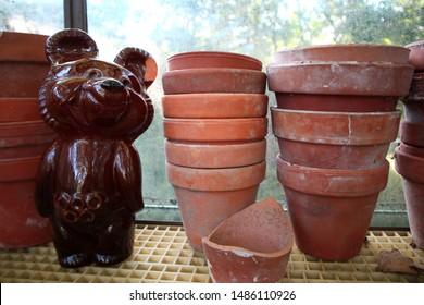 Nurmijarvi, Finland -08-01-2019: Misha, Soviet era Olympic mascot statuette standing on a garden greenhouse shelf with clay pots.