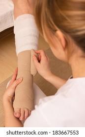 A nurse is applying a pressure bandage on a leg
