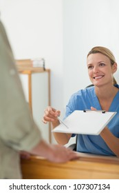 Nurse asking the signature of a patient at a hospital reception