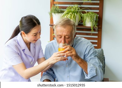 Nurse assist senior man having a cup of orange juice