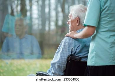 Nurse assisting disabled senior man using wheelchair