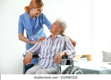 Nurse assisting elderly woman in wheelchair indoors