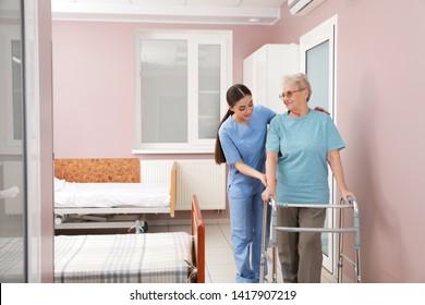 Nurse assisting senior patient with walker in hospital ward