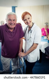 Nurse assisting a senior using a walker in the retirement house