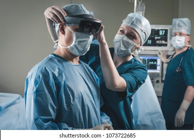 Nurse assisting surgeon with mounting augmented reality holographic hololens glasses before operation