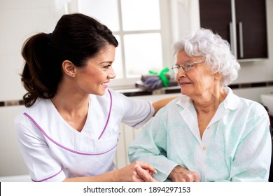 Nurse attending senior woman in a long term care facility, concept of trust between medical staff and home occupants