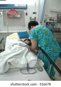 Nurse attends to a child after surgery.