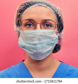 Krankenpflege in einer blauen Uniform und Schutzmaske auf rotem Hintergrund. Porträt einer Ärztin in Brille und einem medizinischen Hut, Nahaufnahme.